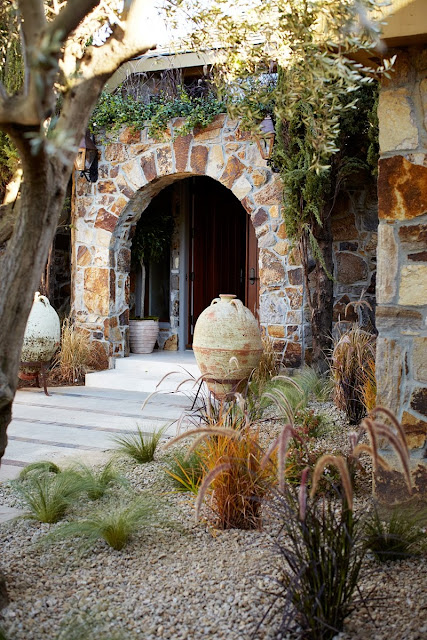 exterior of napa showhouse front door with stone arch and desert plants