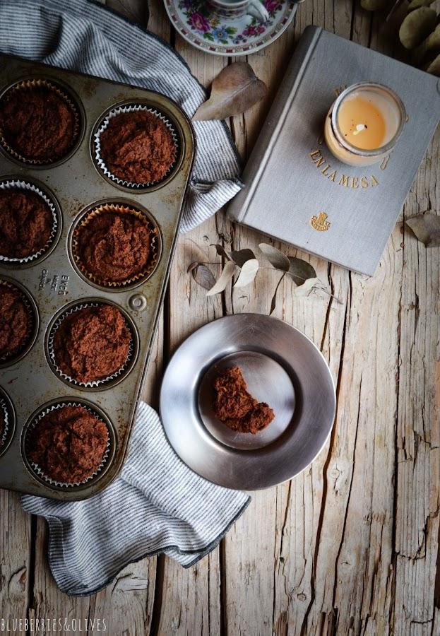 Plan cenital, bandeja de muffins horneados, msesa madera envejecida, paño de lino, plato con pedazo de muffin mordido,ramas eucalipto secas, plato y taza de café porcelana