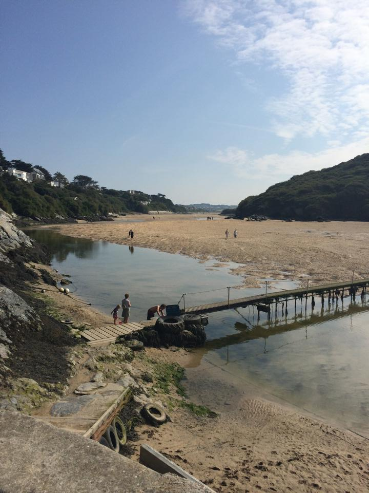 a tidal beach, long sandy beach with a waterway running down the side, bridge leading to a cliff side