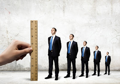 a giant ruler is held next to line-up of businessmen to measure their growth