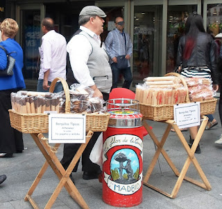 Puesto callejero de barquillero ataviado con el traje típico madrileño. Entre las dos mesas se encuentra la típica barquillera roja con el escudo de la ciudad. En ella antiguamente se guardaba los barquillos e incluye una ruleta en la parte superior.