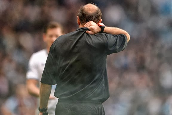 Linesman David Bryan clutches his shirt after being hit by a flare from the crowd