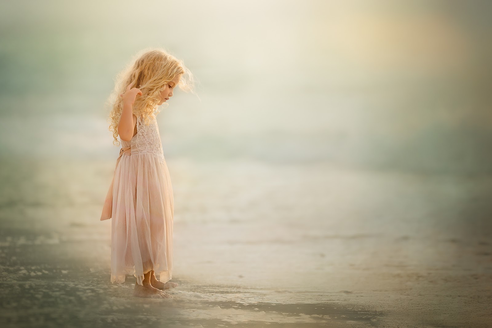 Canon 5D mark III fine art child portrait of a little girl in a pink dress standing with her feet in the caribbean ocean near curacao by Willie Kers