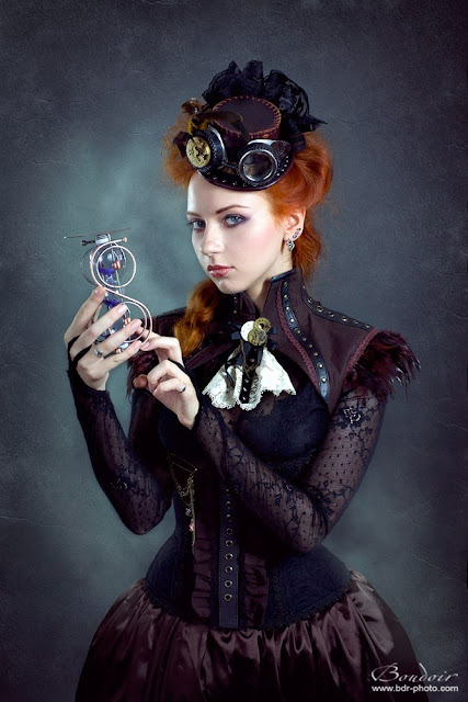 Steampunk redhead woman wearing feathers and lace and steampunk clothing