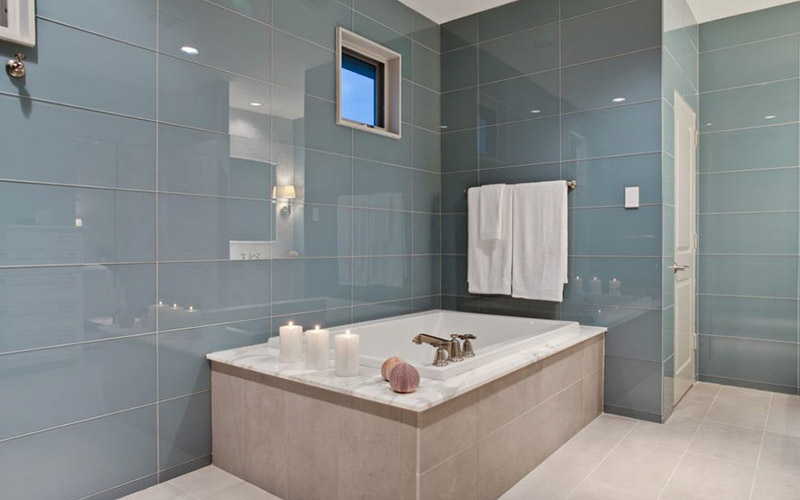 Large format tile transforms the walls and floor of this bathroom