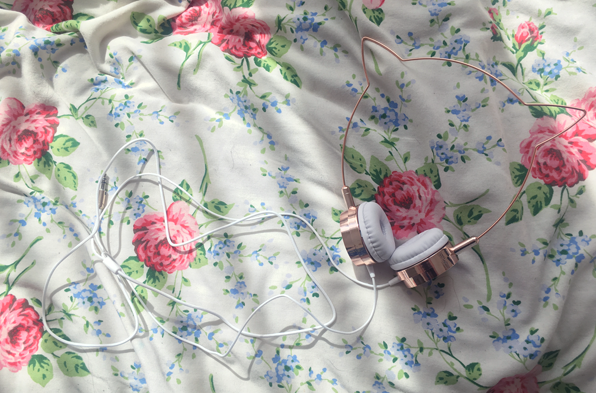 Zara Martin x Skinny Dip Kitty Headphones out of their packaging and on a floral bedspread