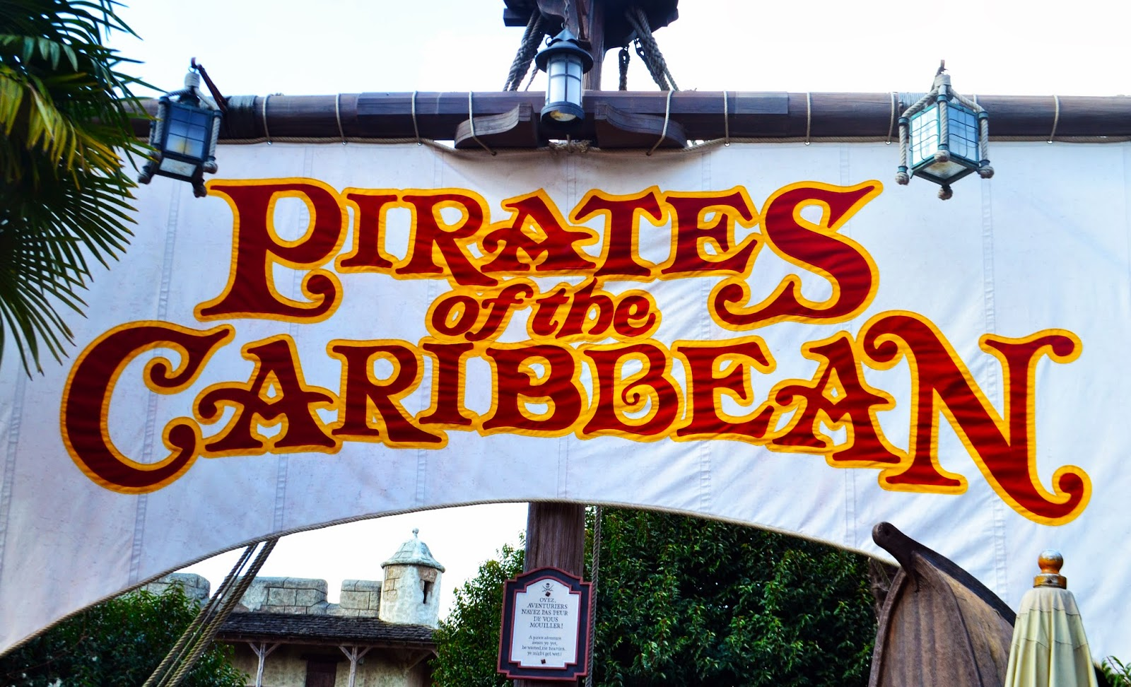 /the entrance sign to the Pirates of the Caribbean ride. The sign os printed on a ships sail