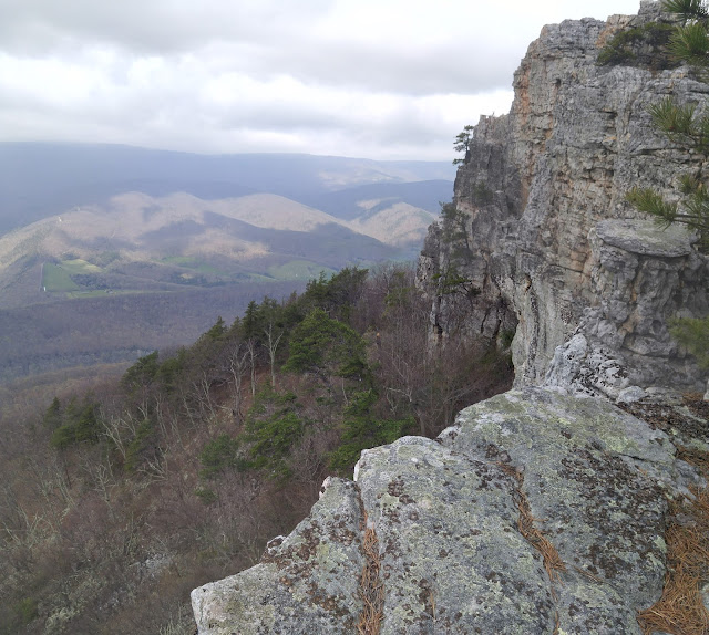 A high wall of exposed sandstone and that ends in the forest slope below. In the background are rolling hills and a partly cloudy sky. North Fork Mountain, West Virginia