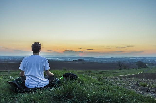 Young boy meditating in a field, facing horizon