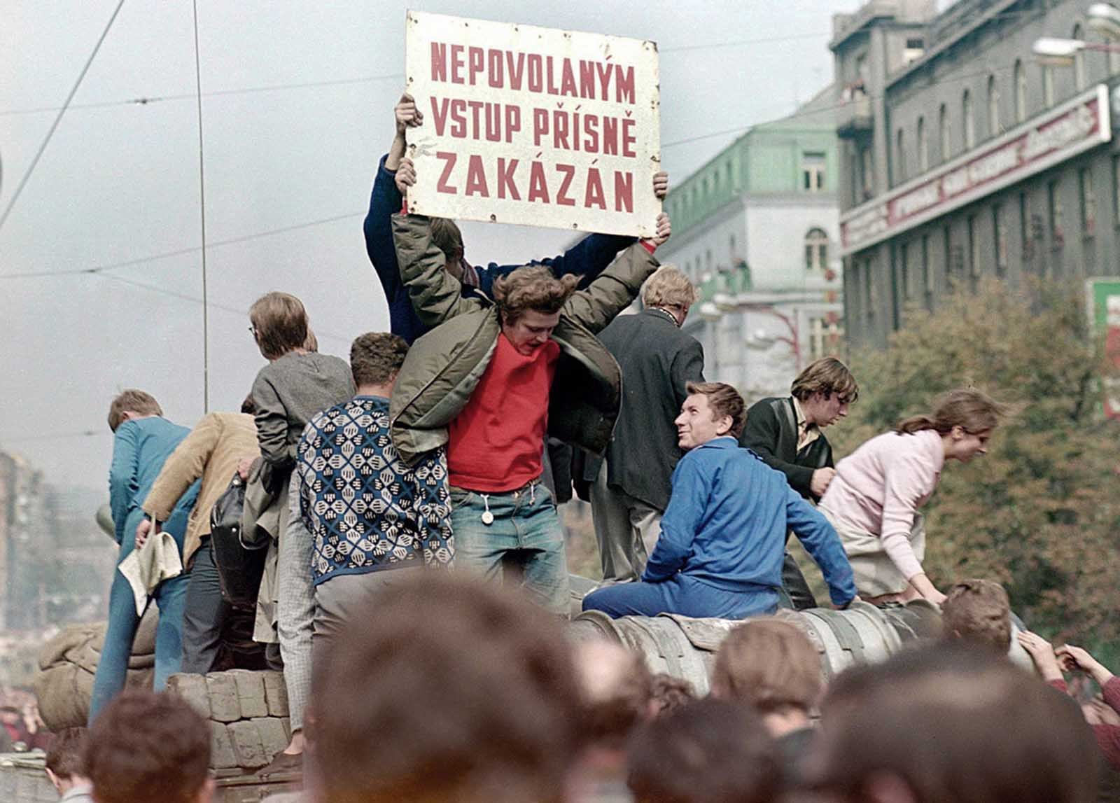 Prague residents ride on top of a Soviet army tank rolling down Wenceslas Square in central Prague during the first day of the Soviet-led invasion, on August 21, 1968. The banner reads: