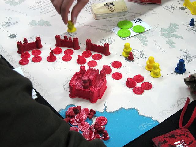 Na imagem mostramos uma área do tabuleiro composto por: uma cartelo com 4 torres, 3 muros e vários círculos que simulavam os terrenos. Além disso, algumas peças na frente simulando o ataque do inimigo.