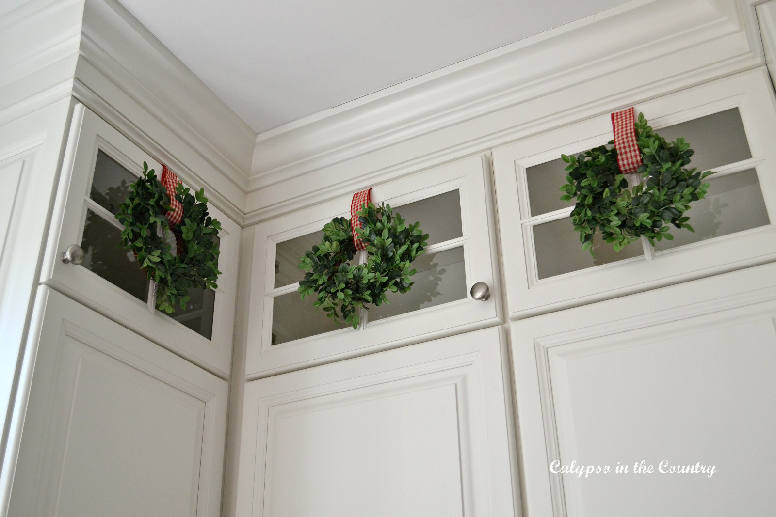 Mini Wreaths on Glass Kitchen Cabinets