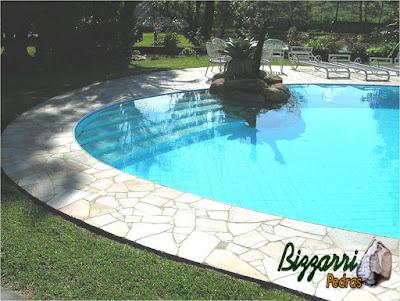 Construção da piscina de alvenaria com cascata de pedra com pedras ornamentais e o piso com pedras Luminárias.