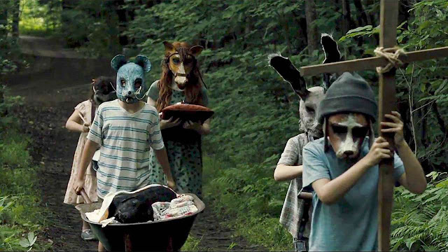 kids in creepy masks holding a funeral procession