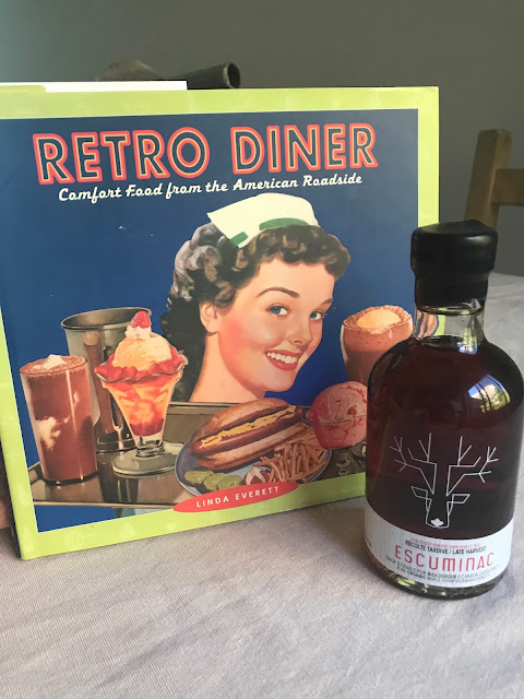 "A Recipe book called ""Retro Diner"" and a bottle of Canadian birch syrup to the right of it"