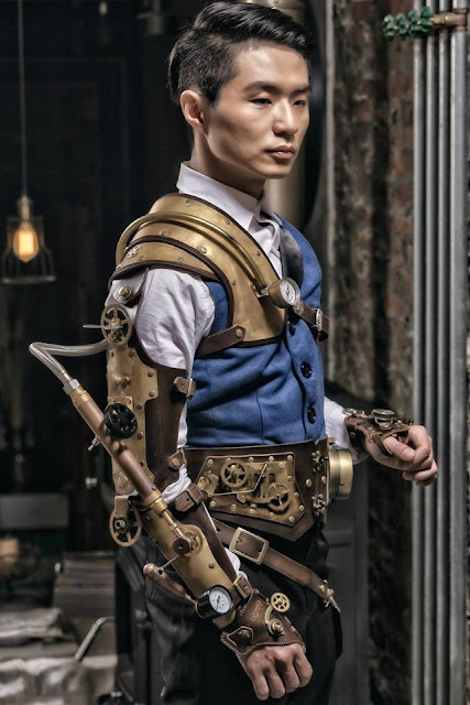 Steampunk man wearing blue waistcoat (vest), trousers, leather armor, leather steam arm. Men's steampunk fashion and costumes