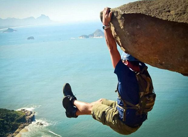 This is Luis Fernando Candela. He claims to have prepared for this moment for months at the gym. The rock he's hanging from is 984 feet above the beach. - This Viral Photo Inspired Copycats, But There's Something You Should Know…