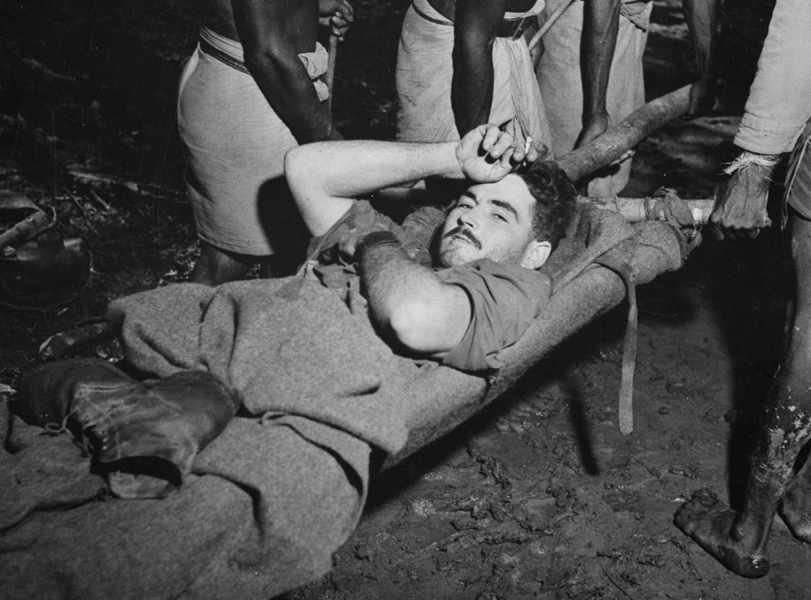Los camilleros llevan al cabo R.D. Somerville a una estación de preparación después de una batalla en Oive.