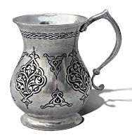 Üzerinde siyah işlemeler olan gümüş renkli maşrapa