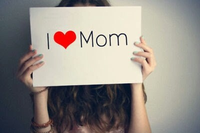 girl holding i love you mom board