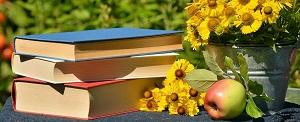 foto di libri su tavolo con fiori
