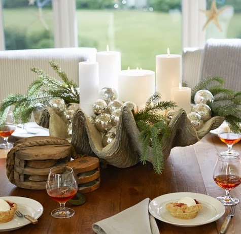 this coastal christmas holiday table decor idea comes from pottery barn a giant clam shell holds christmas ball ornaments and holiday greenery