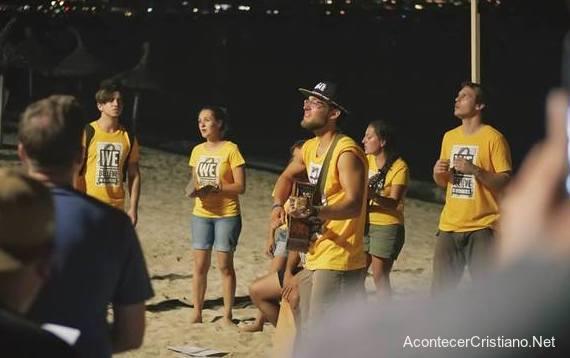 Jóvenes compartiendo el Evangelio en la playa