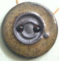 "Dark olive green and black button with a center motif: the holes are ""pinned"" using black beads as anchors."