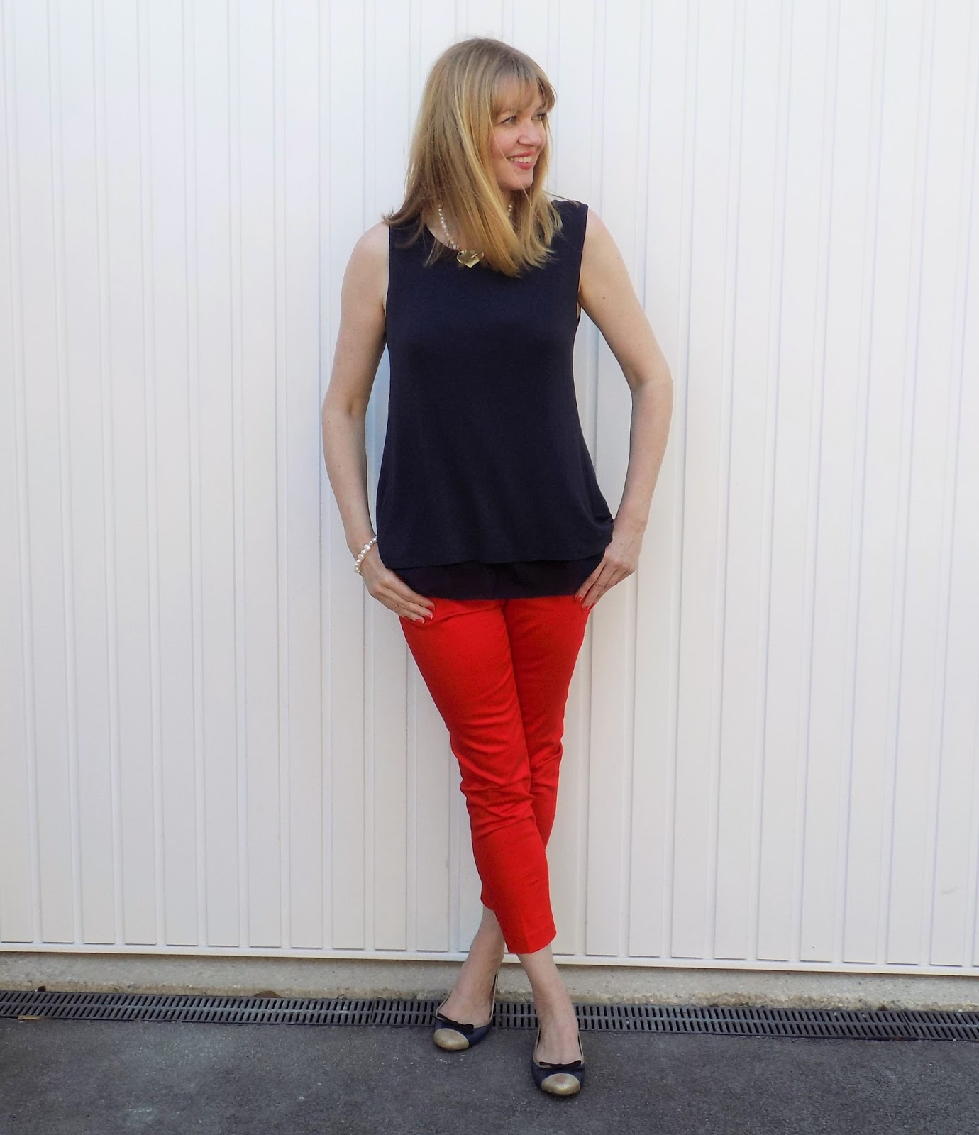 Red trousers, freshwater pearl jewellery and navy and gold ballerina shoes
