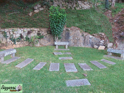 Banco de pedra com pedra folheta com os caminhos de pedra folheta no jardim.