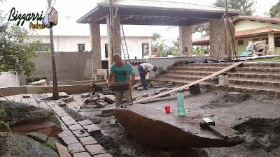 Execução de revestimento com pedras do rio nos pilares de concreto com a escada de pedra folheta com o calçamento de pedra folheta.