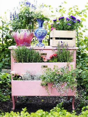 Cajonera rosa con plantas en sus cajones.