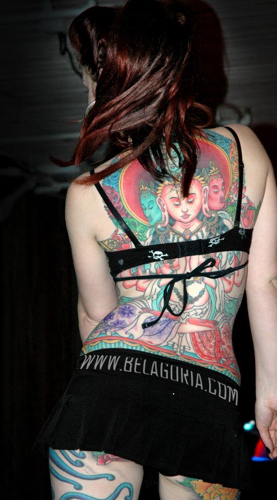 vemos a una pole girl en un club nocturno bailando, lleva tatuaje en la espalda de un buda