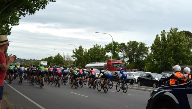 A rear view of the peloton heading south up the triple-laned carriageway of Marion Road from Sturt Road on the way to the Southern Expressway gate. In the distance is an overhead traffic sign indicating the start of the expressway. Crowds are lining the left hand side of the road. A man in a red shirt and dark shorts wearing a white hat (with black hat band) is standing at the side of the road and applauding the riders.  The front left fender of a support vehicle can be seen in the bottom right corner of the picture. Traffic can be seen on the northbound carriageway waiting for the road intersectionto re-open.