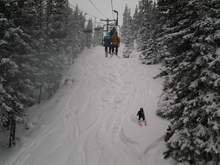 Winter snowy day with a skier skiing in powder on a steep hill below the chair lift.