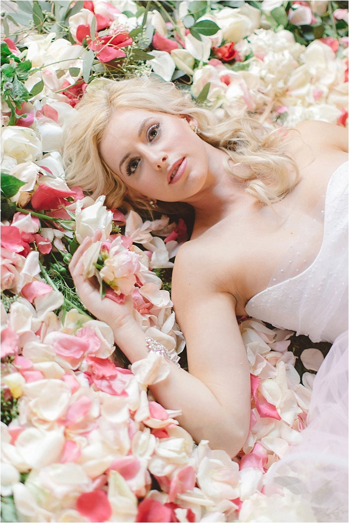 Gorgeous photo of bride laying in rose petals