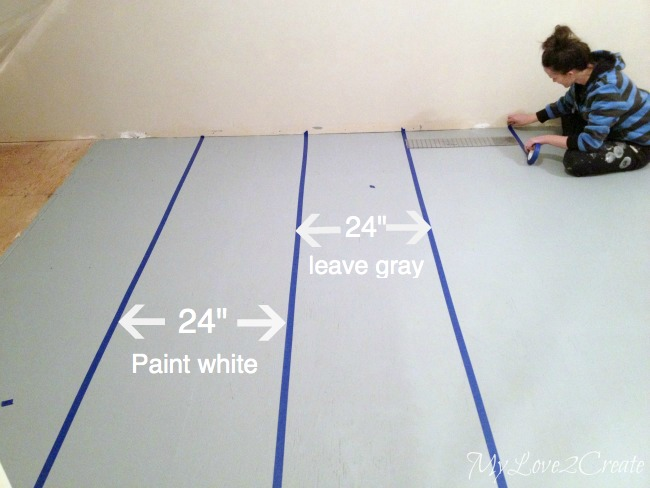 measuring and taping stripes on subfloor to be painted