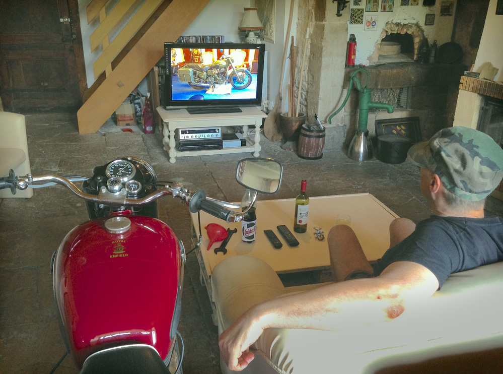 Man and motorcycle watch television together.