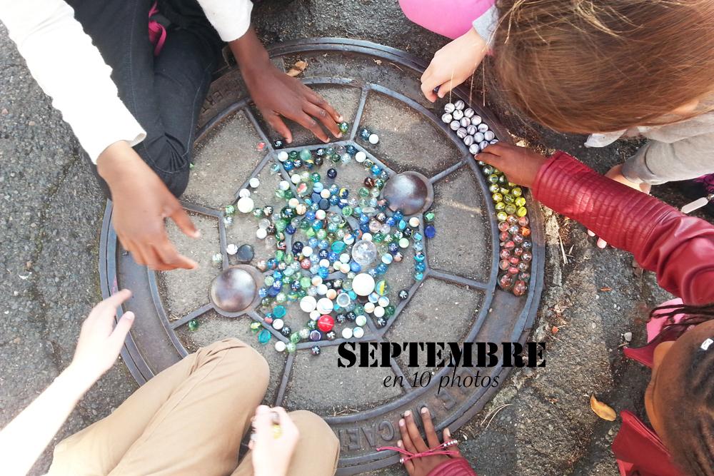 Des enfants jouent aux billes dans une cour de récréation