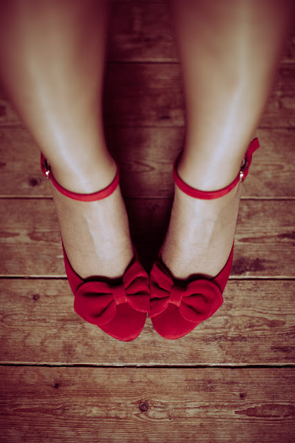 View of a women's legs and feet wearing red rockabilly suade shoes with bows