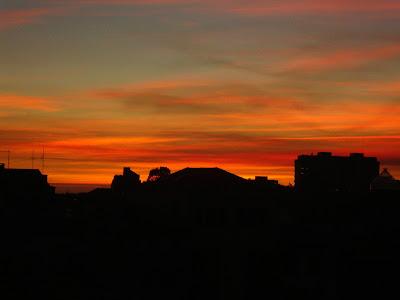 Wspaniała panorama na Porto i ocean w oddali, przy zachodzącym słońcu.