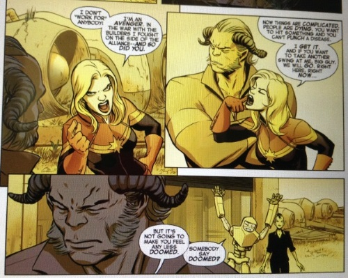 Three panels. In the first, Carol points at a horned alien and says, 'I don't 'work for' anybody! I'm an Avenger. In the war with the Builders, I fought on the side of the Alliance--and so did you.' In the second panel, she points at her cheek and says, 'Now things are complicated. People are dying. You want to hit something and you can't punch a disease. I get it. And if you want to take another swing at me, big guy, we will go, right here, right now...' The third panel is a close in shot of the alien's face, with another armoured alien behind him. Carol's dialogue reads, 'But it's not going to make you feel any less doomed.' The armoured alien's reads, 'Somebody say doomed?'