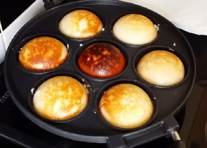 Frying coconut and rice donut (Vitumbua) in a pan