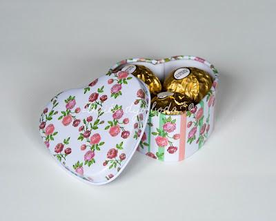 Caja metálica con estampado de flores conteniendo tres bombones