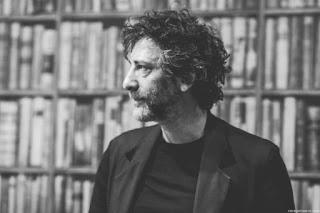 Fotografía de Neil Gaiman de perfil, vistiendo una chaqueta oscura, camiseta negra. Detrás hay una estantería con libros.