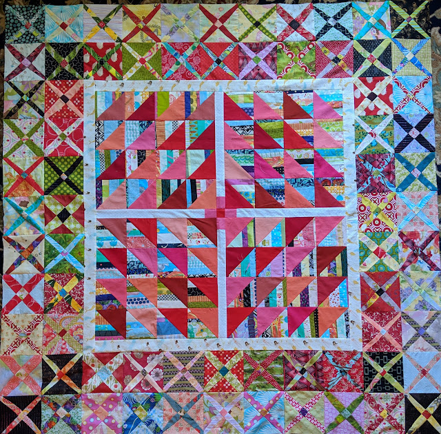 The top is made of multi-color striped triangles paired with reds. There are two rows of Crossroads blocks as an outer border.