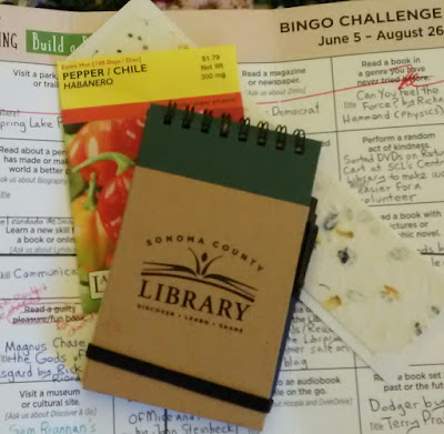 Partial view of Bingo Challenge card that has typeset challenges with handwritten entries in the grids. Stacked on top of the Bingo sheet are a small notebook with logo of Sonoma County Library, seed packet for Habanero Peppers and rough-paper bookmark with seeds embedded in it