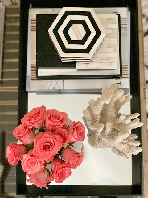 Coral and coral hued roses in a black tray in a room designed by Sherry Hart. Come discover more inspiring trays for layering and vignettes in Adding Tray Très Chic to Your Home.