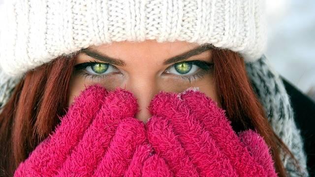 Mulher com luvas e touca para o frio