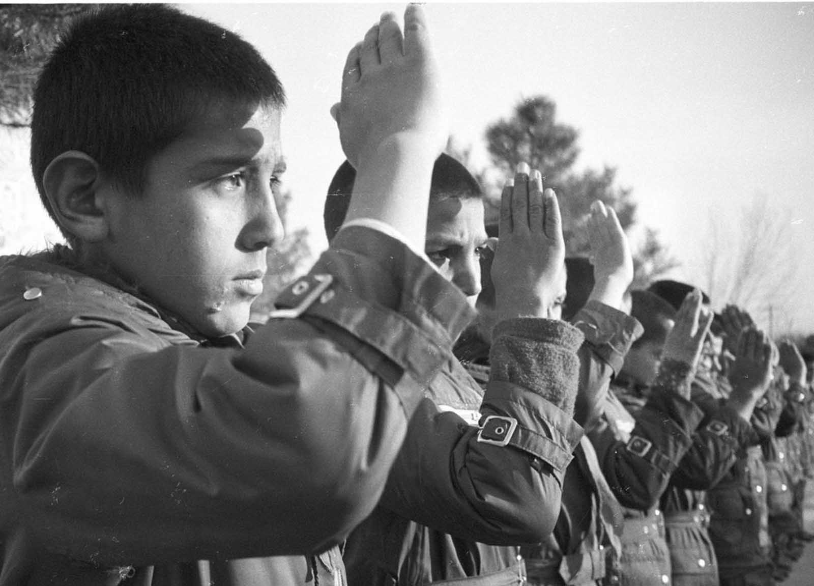 Afghan boys orphaned by the war between Kabul's Soviet-backed government and Muslim rebels salute visitors at the Watan ('Homeland') Nursery in Kabul on January 20, 1986. Communist political education started young in Kabul schools during the occupation, as part of the government's drive to win the population over.